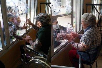 Adultos mayores de un geriátrico dan abrazos a sus seres queridos a través de una ventana intervenida
